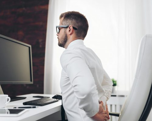 Office worker with back pain from sitting at desk all day